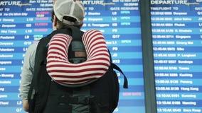 背包徒步旅行者关于数字式日程表显示的检验飞行信息在iairport 影视素材