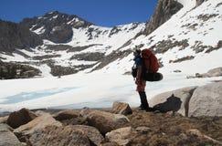 背包徒步旅行者冻结的湖 库存图片