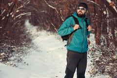 背包徒步旅行者在冬天森林里 免版税库存图片