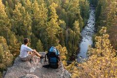 背包徒步旅行者坐岩石和神色在美丽的景色 免版税图库摄影