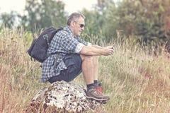 背包徒步旅行者坐岩石 免版税库存照片