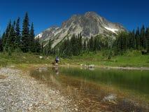 背包徒步旅行者女性湖边 免版税库存图片