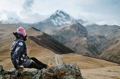 年轻背包徒步旅行者妇女坐在高加索山脉的一个岩石 免版税图库摄影