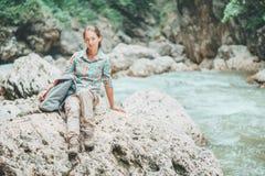 背包徒步旅行者妇女坐河岸 库存图片