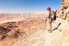 背包徒步旅行者妇女旅游常设沙漠山峭壁边缘lan 免版税图库摄影