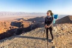 背包徒步旅行者少妇常设沙漠山边缘峡谷视图 图库摄影