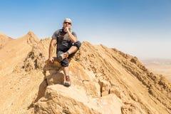 背包徒步旅行者旅游坐的沙漠山峭壁土坎边缘风景 免版税图库摄影