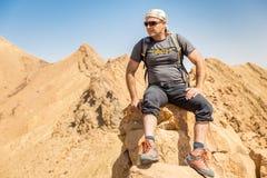 背包徒步旅行者旅游坐的沙漠山峭壁土坎边缘风景 免版税库存图片