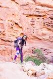背包徒步旅行者旅游妇女常设沙漠石头峡谷山t 库存图片