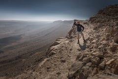 背包徒步旅行者旅游常设山峭壁土坎边缘夜土地 库存照片