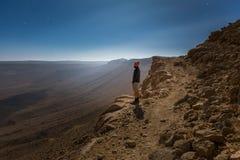 背包徒步旅行者旅游常设山峭壁土坎边缘夜土地 免版税图库摄影