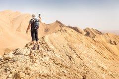 背包徒步旅行者旅游常设沙漠山峭壁土坎边缘风景 免版税库存图片