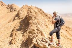 背包徒步旅行者旅游常设沙漠山峭壁土坎边缘风景 图库摄影
