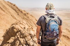 背包徒步旅行者旅游常设沙漠山峭壁土坎边缘风景 库存照片
