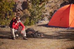 背包徒步旅行者有休息在橙色帐篷,从杯子的饮料茶附近 免版税库存照片