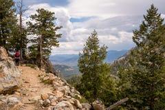 背包徒步旅行者朝向一列狭窄的岩石火车在爱达荷山 免版税图库摄影