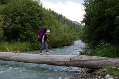 背包徒步旅行者横穿河 库存图片