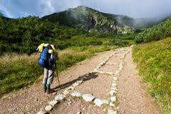 背包徒步旅行者测试的女孩山 免版税库存图片