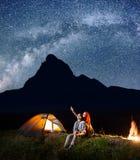 背包徒步旅行者看的女孩和人在晚上发光满天星斗的天空 坐在帐篷和营火附近的年轻夫妇 库存照片