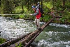 背包徒步旅行者穿过山河 库存照片