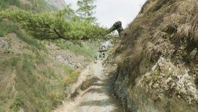 背包徒步旅行者通过在尼泊尔道路的门走在马纳斯卢峰山附近 股票录像