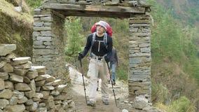 背包徒步旅行者通过在尼泊尔道路的门走在马纳斯卢峰山附近 股票视频