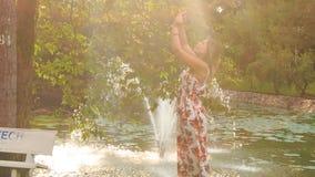 背后照明侧视图白肤金发的女孩由喷泉做Selfie在公园 影视素材