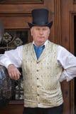 背心和圆顶硬礼帽的一个时髦的减速火箭的葡萄酒时兴的绅士邀请游人进入stre的餐馆 库存照片