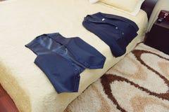 背心和夹克在床上 免版税库存照片
