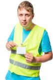 背心的工作者显示他的在白色的徽章 免版税库存照片