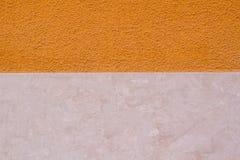 背景上色二墙壁 桔子被绘的和米黄大理石墙壁 库存图片