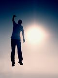 背景下来落的飞行人天空年轻人 年轻人落 世故人剪影  库存图片