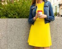 背景中断咖啡新月形面包杯子甜点 一件美丽的黄色夏天礼服的女孩休息用一份咖啡在一个夏日在欧洲城市 一部分的t 免版税库存图片