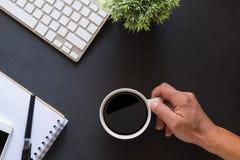 背景中断咖啡新月形面包杯子甜点 拿着在工作书桌上的手特写镜头顶视图杯子 免版税库存照片