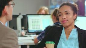 背景中断咖啡新月形面包杯子甜点 非洲年轻女人谈话与她的同事 股票录像