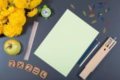 背景五颜六色的学校 与时钟,苹果,厨师的书桌表面 库存图片