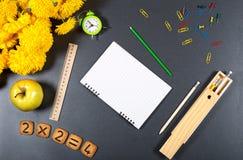 背景五颜六色的学校 与时钟,苹果,厨师的书桌表面 免版税库存照片