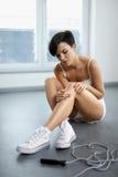 背景伤害查出的行程白色 在膝盖,痛苦的膝盖的美好的妇女感觉痛苦 免版税库存照片