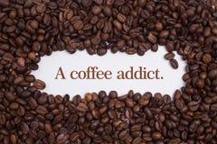 背景做了在心脏形状的咖啡豆与消息` A咖啡上瘾者 ` 免版税库存图片