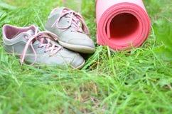背景健康生活方式 瑜伽席子,体育鞋子,瓶在草背景的水 健康的概念和体育生活 库存照片