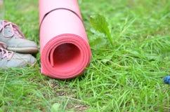 背景健康生活方式 瑜伽席子,体育鞋子,瓶在草背景的水 健康的概念和体育生活 库存图片
