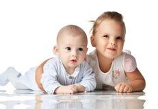 背景兄弟查出的姐妹白色 四个月的婴儿男婴和两岁女孩说谎小孩的孩子一起拥抱愉快微笑 图库摄影