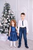 背景兄弟查出的姐妹白色 圣诞节内部 3个照相机长沙发系列女孩查找关于坐的母亲橙色纵向他们那里 小的子项 库存照片