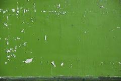 背景剥了在墙壁上的橄榄色的浅绿色的油漆 库存照片