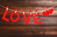 背景华伦泰` s天 两红色心脏和词爱在木头 库存照片
