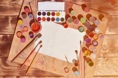 背景图象在水彩绘画和艺术上的表示兴趣 一张空白的纸片,围拢由刷子,有waterc的罐头 免版税库存图片