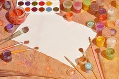 背景图象在水彩绘画和艺术上的表示兴趣 一张空白的纸片,围拢由刷子,有waterc的罐头 免版税库存照片