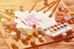 背景图象在水彩绘画和艺术上的表示兴趣 一张被绘的纸片,围拢由刷子,瓶子waterc 免版税库存图片