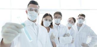 背景图象是一个小组医护人员与液体一起使用在实验室 库存图片