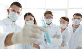 背景图象是一个小组医护人员与液体一起使用在实验室 免版税库存照片